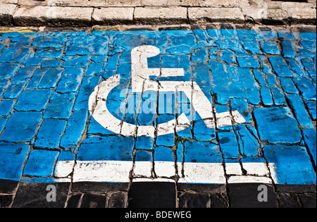 Disabled parking bay on cobbled street. - Stock Photo