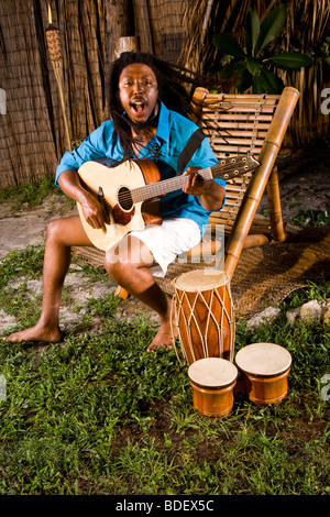 Young Jamaican man with dreadlocks playing guitar and bongos on tropical island - Stock Photo