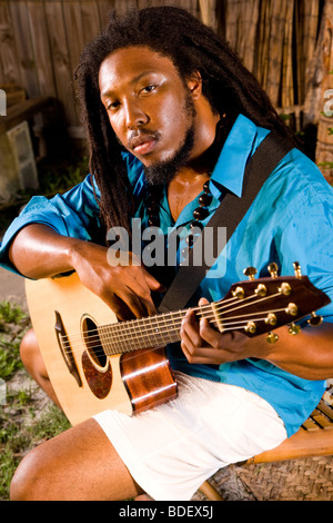 Portrait of young Jamaican man with dreadlocks holding guitar on tropical island - Stock Photo