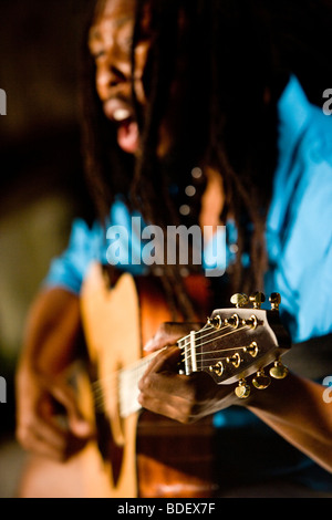 Young Jamaican man with dreadlocks playing guitar on tropical island - Stock Photo