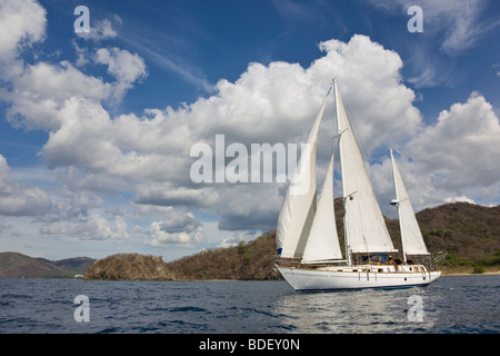 Ketch rig sailboat cruising along the shoreline in the Papagayo Bay, Guanacaste, Costa Rica. - Stock Photo