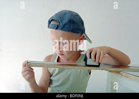 child measuring wooden plank - Stock Photo
