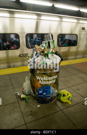 A trash can overflowing with beer cans and bottles collected by Metro North car cleaners is seen in Grand Central - Stock Photo