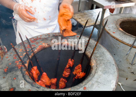 Tandoori chicken is prepared at a street fair following the Indian Independence Day Parade in New York - Stock Photo