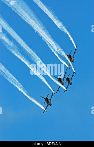 A formation of four BAE Hawk jets passing at a low altitude - Stock Photo