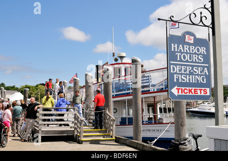 Hyannis Harbor, Cape Cod harbor tours and deep sea fishing sign and boat in summer with people on docks and boarding - Stock Photo