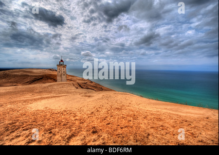 Lighthouse in the sand dunes of Rubjerg Knude in Denmark - Stock Photo