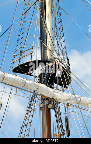 Sailing ship mast detail with sail furled on yardarm, mast top, shrouds, lines, rigging and halyards - Stock Photo