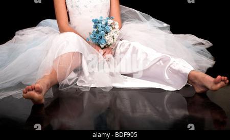 happy bride sitting on the black floor - Stock Photo