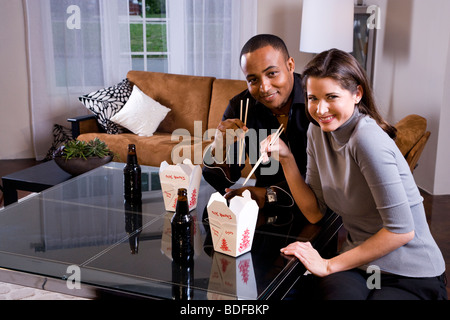 Multi-ethnic couple eating Chinese take-out in living room - Stock Photo