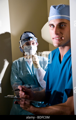 Portrait of two healthcare workers in scrubs with clipboard - Stock Photo