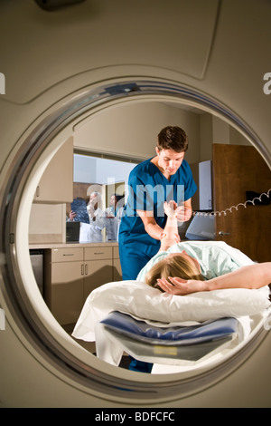Patient lying on CAT scan machine while healthcare worker takes pulse - Stock Photo