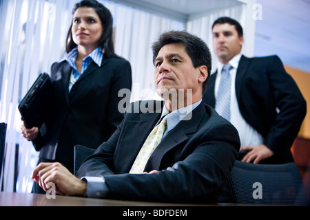 Hispanic businessman in meeting with younger colleagues behind - Stock Photo