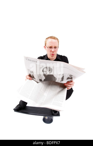 young man on board reading newspaper and balancing on roll - Stock Photo