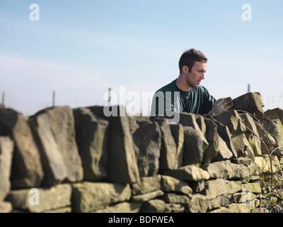 Man Inspecting Dry Stone Wall - Stock Photo