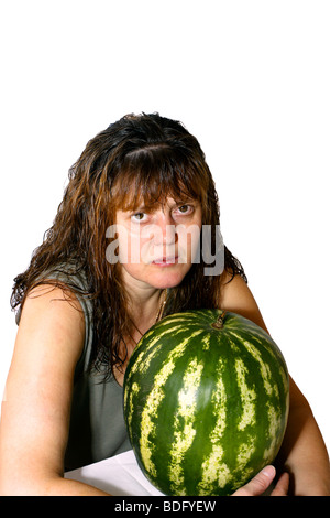the woman with a water-melon and wet hair, attentively looks forward - Stock Photo