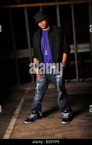 African American hip hop dancer standing over industrial background - Stock Photo