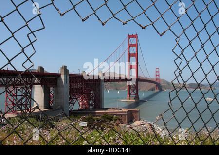 The Golden Gate Bridge viewed through a hole in a chain link fence San Francisco California USA - Stock Photo