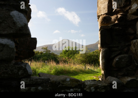looking out at Slieve Donard in the mourne mountains from the ruins of maghera old church founded by St Donard - Stock Photo
