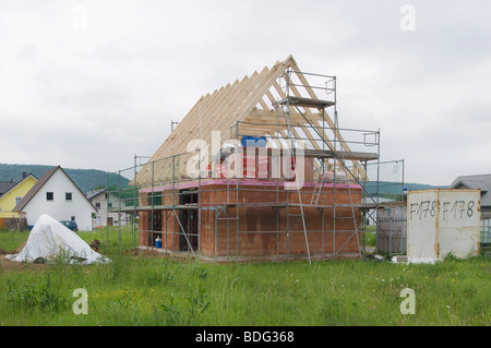 House construction, scaffolding with roof truss in a new housing estate - Stock Photo