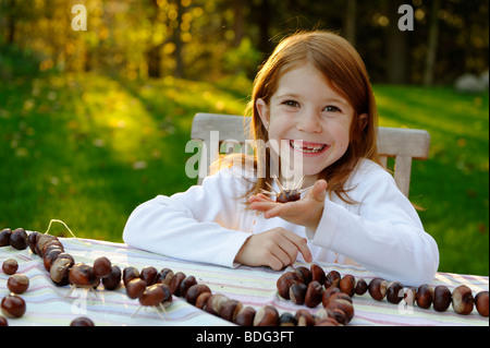 Girl is playing in the garden with chestnuts, chestnut hedgehog, chestnut figures - Stock Photo