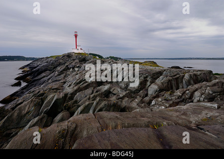 Cape Forchu peninsula and lighthouse on the Atlantic Ocean with wet rocks at Yarmouth Harbour Nova Scotia - Stock Photo