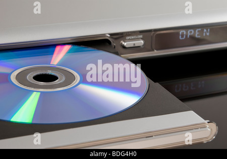 DVD disc inserted in DVD player disc tray isolated on black background - Stock Photo