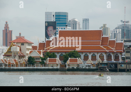 Temple and picture of the Thai king Bhumibol seen from across the Chao Phraya River in Bangkok - Stock Photo
