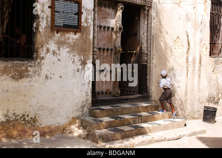 Stone Town, the main town on Zanzibar is famous for it's beautiful old carved wood doors. A boy walks up the steps - Stock Photo