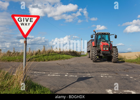 Tractor at crossroads with Give Way sign - Stock Photo