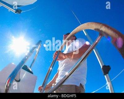 A skipper steering on board a yacht under blue skies while cruising in Pittwater on the North Shore from Sydney, - Stock Photo