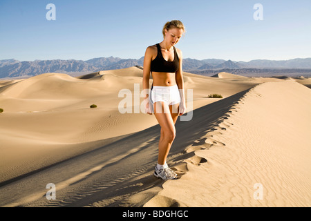 A young woman in running clothes standing on a 200ft sand dune on a sunny day. - Stock Photo
