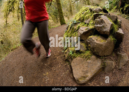 A woman running up a trail through a green, mossy forest in Silver Falls State Park, Oregon, USA.