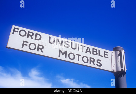 Black and white finger-post on grey pole under blue sky with cirrus cloud stating Ford Unsuitable for Motors - Stock Photo