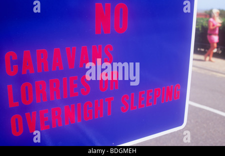 Detail of luminescent blue and red sign stating No Caravans Lorries or Overnight sleeping and with woman walking - Stock Photo