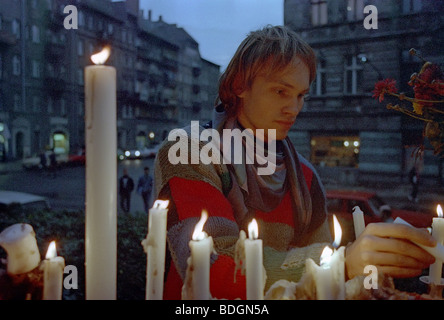 Young man igniting candles in front of Gethsemane Church during the demonstration in 1989, Berlin, GDR - Stock Photo