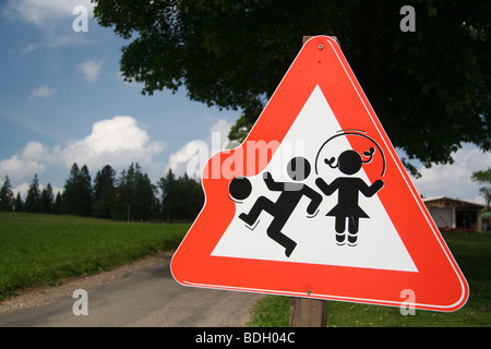 Triangular street sign warning traffic of children playing on the road, a village in the Jura, Switzerland - Stock Photo