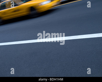 A New York yellow cab in motion on the street. - Stock Photo