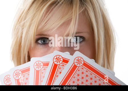 young 20 year old blonde woman holding five large playing cards over her face - Stock Photo