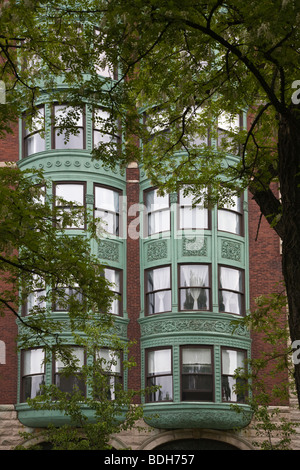 Brick Apartment Building Window apartment windows in building with american flag flying from one