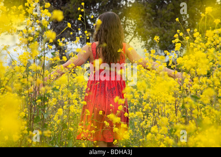 Young woman in a red dress with her hands outstretched walking to the beach through a field of yellow flowers. - Stock Photo