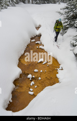 A woman backcountry skiing next to a mineralized creek on Red Mountain Pass, Ouray, Colorado. - Stock Photo