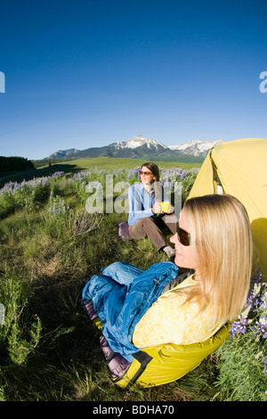Two women sit and enjoy the view while camping in field of flowers, Telluride, Colorado. - Stock Photo