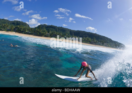 A wide angle, fisheye view of a woman surfing at Pipeline, on the north shore of Oahu, Hawaii. Stock Photo