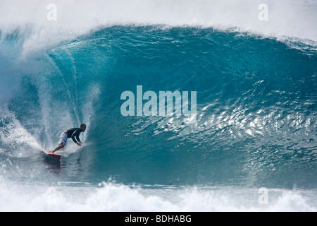 A young man surfing a big wave at Pipeline, on the north shore of Oahu, Hawaii. Stock Photo