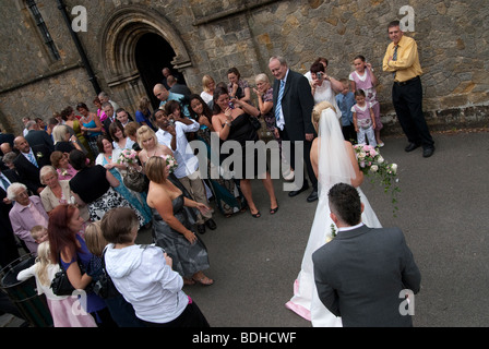 bride and groom and guests outside church - Stock Photo