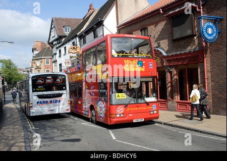 Double decker open top sightseeing bus passing a single decker bus in the narrow streets of the city or York, England - Stock Photo