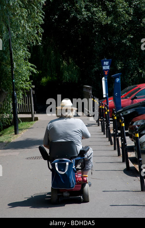 Elderly man on a mobility scooter in an english town centre - Stock Photo
