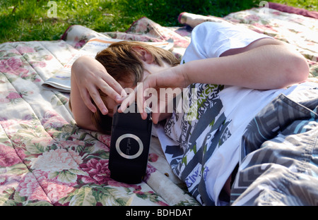 Young boy lying on rug outside playing on a psp computer - Stock Photo