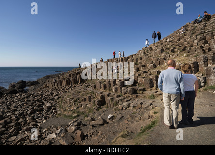 A couple studying the rock formations at the Giant's Causeway. - Stock Photo